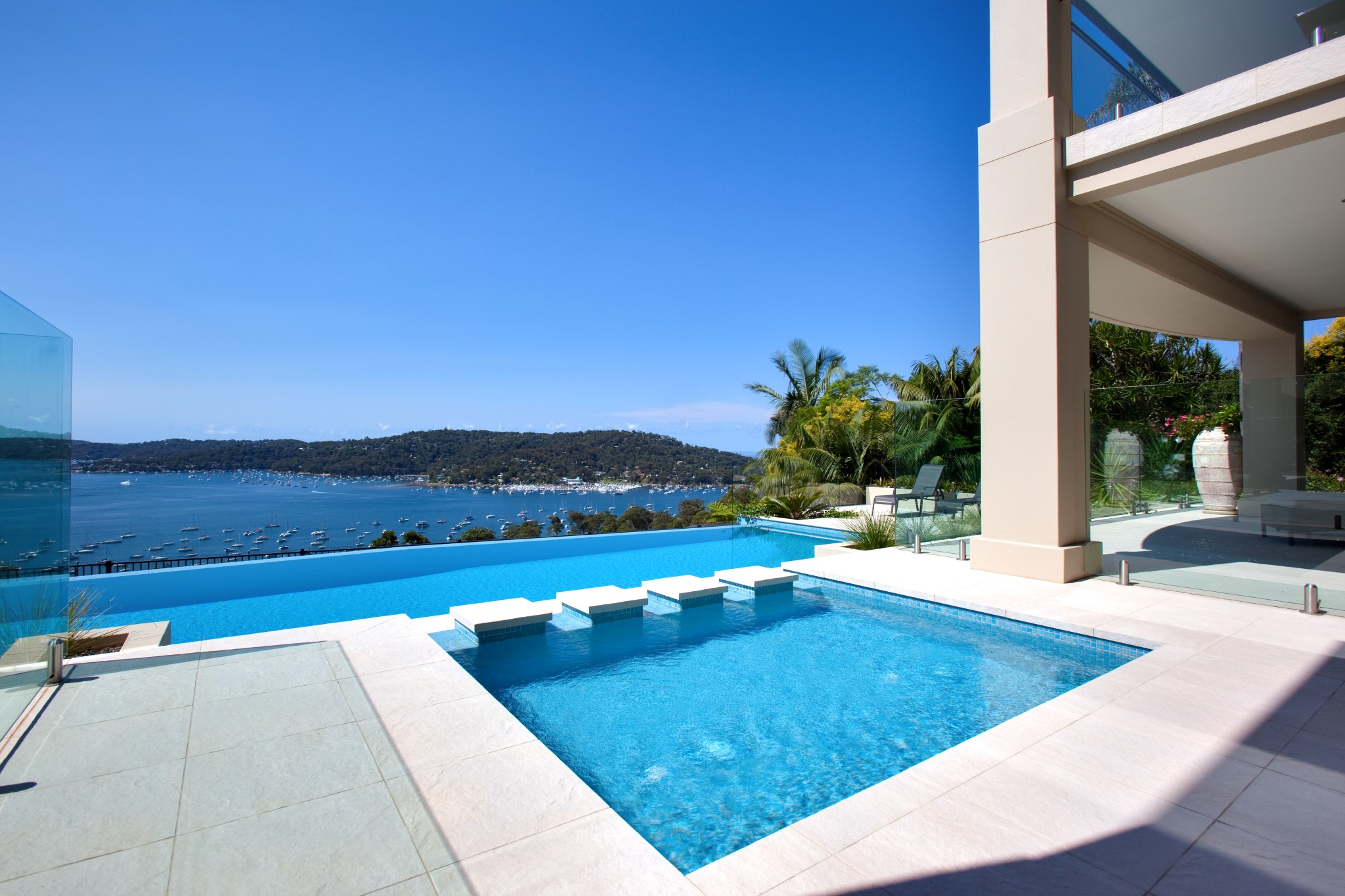 Beautiful blue fresh infinity swimming pool with an amazing sea view in Bayview