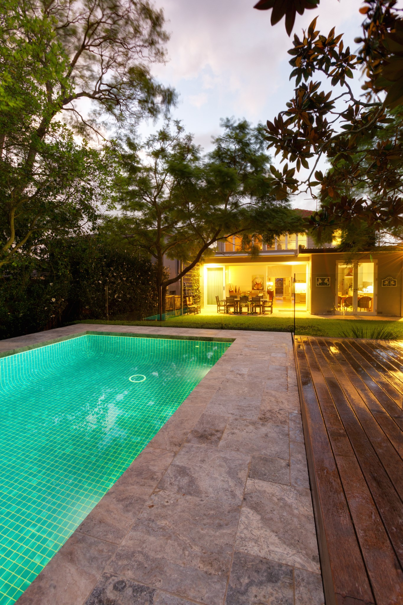 Lap pool and cozy house with turning lights on